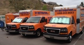 Water and Mold Damage Restoration Vehicles At Job Site